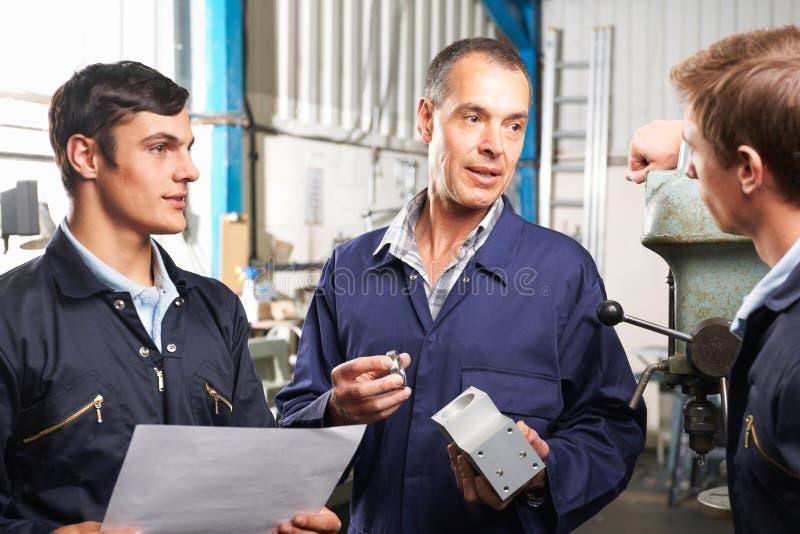 Команда инженеров имея обсуждение в фабрике стоковое фото