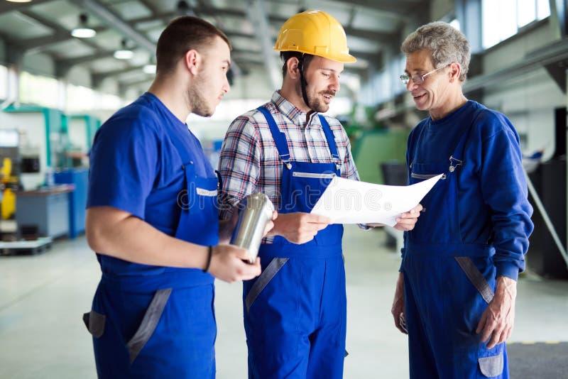 Команда инженеров имея обсуждение в фабрике стоковые фото