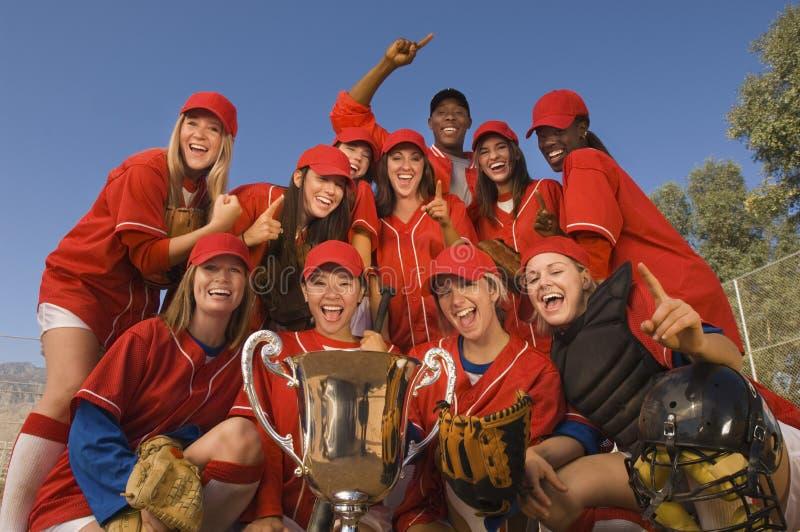 Команда и тренер софтбола с трофеем празднуя против неба стоковое изображение