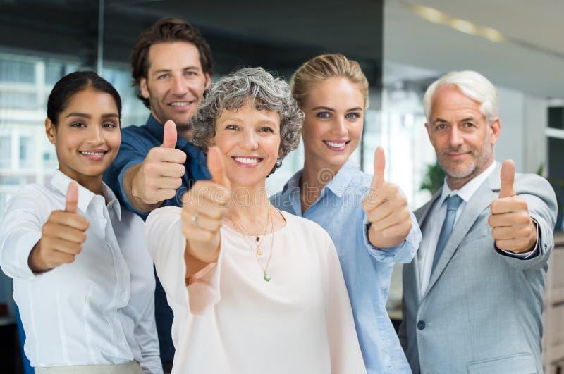 Команда показывая большие пальцы руки вверх стоковая фотография rf