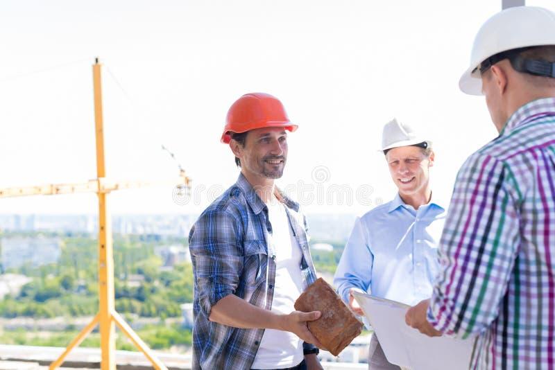 Команда построителей на строительной площадке, подрядчик давая кирпичу подмастерья новый старт проекта строительства стоковая фотография