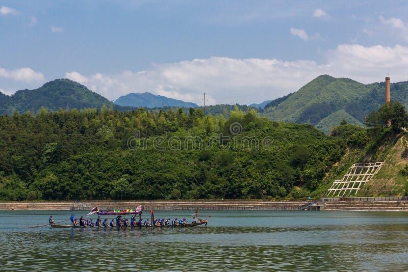 Команда фестиваля шлюпки дракона фиолетовая пересекает реку стоковые фотографии rf