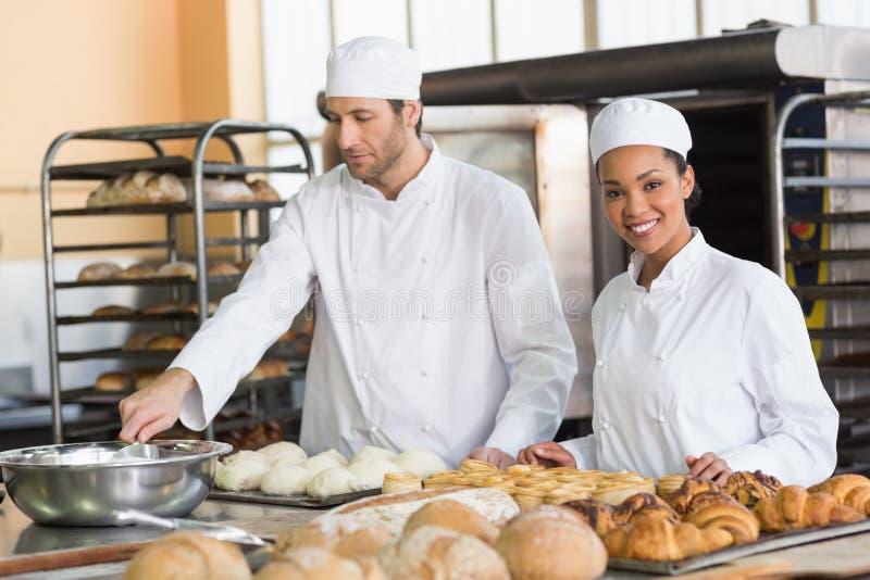 Команда хлебопеков подготавливая тесто и печенье стоковая фотография