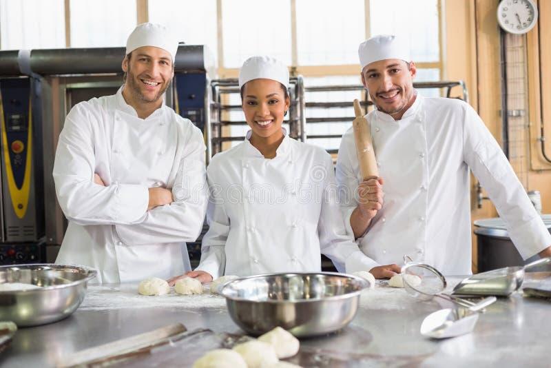 Команда хлебопеков подготавливая тесто стоковые изображения rf