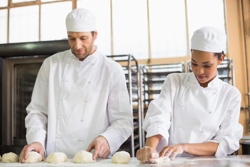 Команда хлебопеков подготавливая тесто стоковые изображения