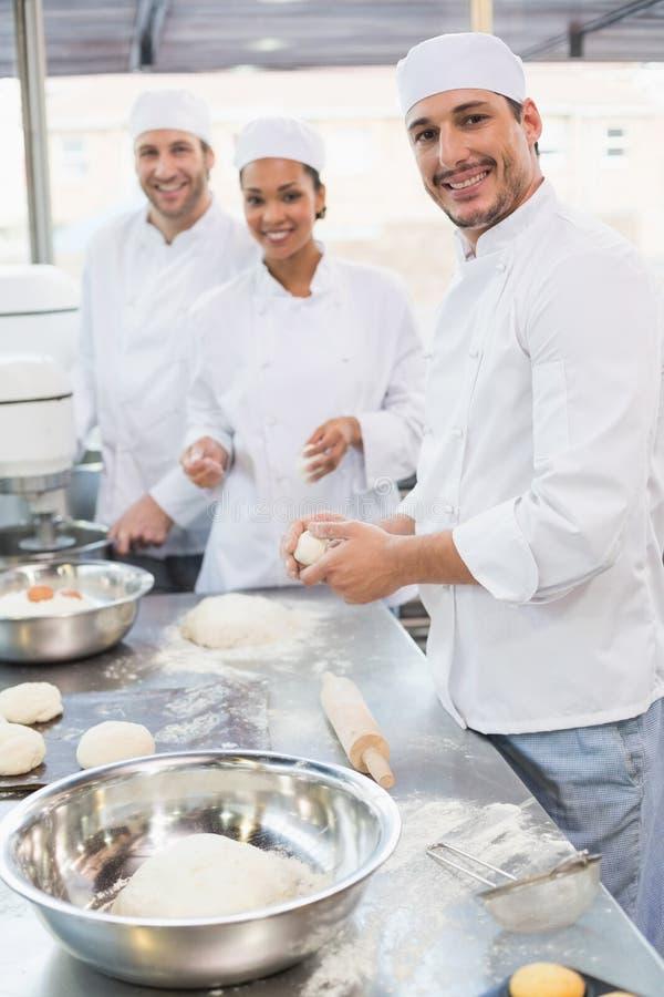 Команда хлебопеков работая на счетчике стоковое фото