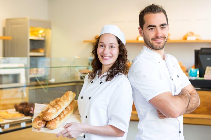 Команда хлебопеков работая на хлебопекарне стоковое изображение