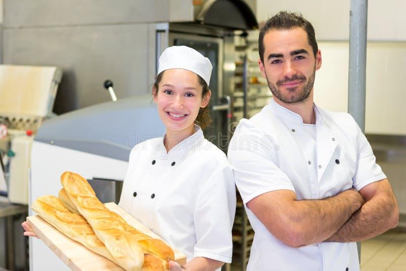 Команда хлебопеков работая на хлебопекарне стоковые изображения