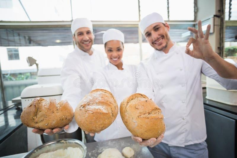 Команда хлебопеков усмехаясь на камере держа хлеб стоковые фото
