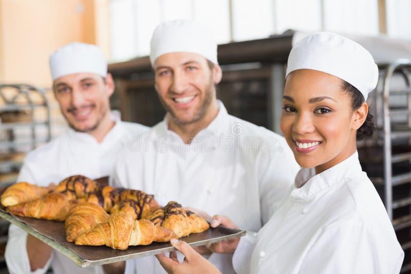 Команда хлебопеков усмехаясь на камере с подносами круассанов стоковое фото rf