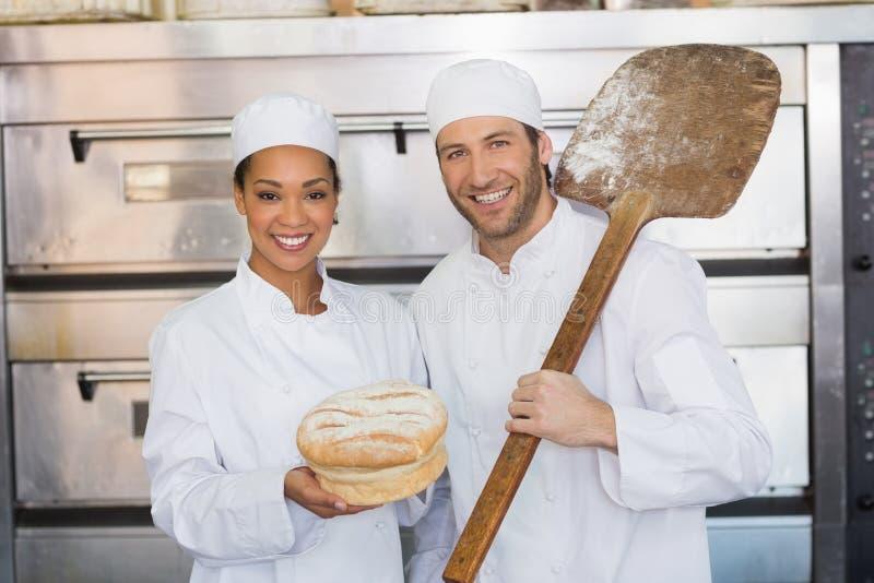 Команда хлебопеков усмехаясь на камере с хлебцем стоковая фотография