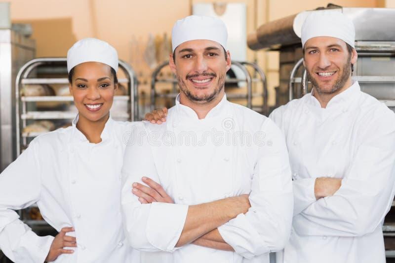 Команда хлебопеков усмехаясь на камере стоковое изображение rf