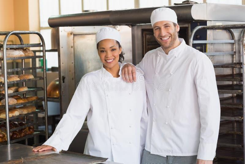 Команда хлебопеков усмехаясь на камере стоковое фото rf