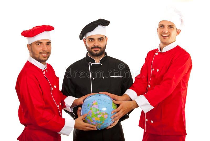 Команда шеф-поваров держа глобус мира стоковая фотография