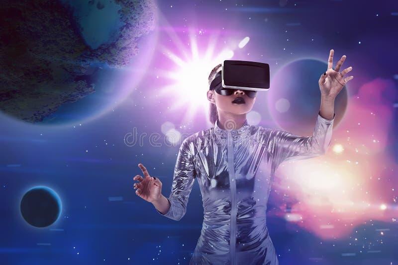 Комбинезон латекса довольно азиатской женщины нося серебряный и шлемофон VR стоковая фотография