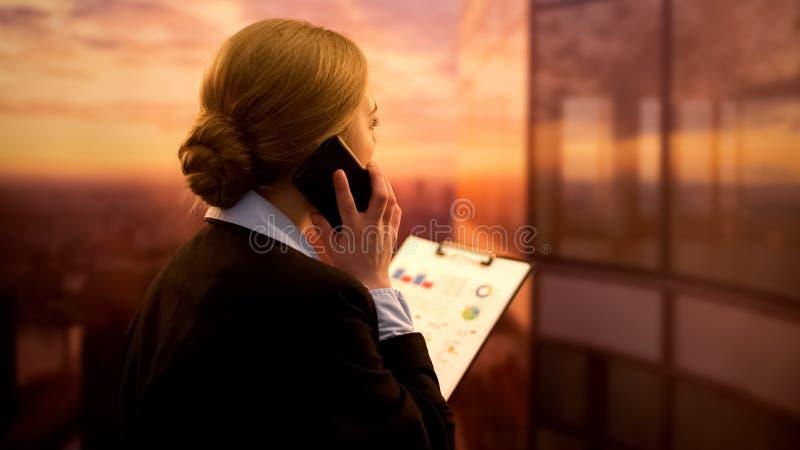 Коммерсантка вызывая коллеги для проверки финансового отчета, представления компании стоковое изображение rf