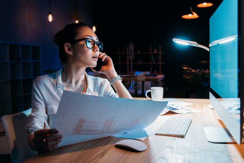 Коммерсантка в eyeglasses держа светокопию и говоря на smartphone стоковые фото