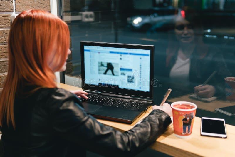 Коммерсантка, девушка держа ручку, писать в тетради, ноутбук в кафе, смартфоне, ручке, компьютере пользы r стоковая фотография rf