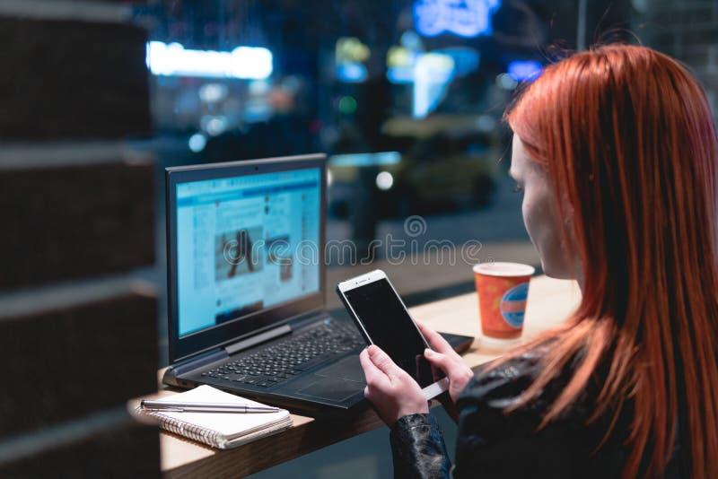 Коммерсантка, девушка работая на ноутбуке в кафе, смартфоне в руках, ручке владением, телефоне пользы r Онлайн, стоковое фото rf