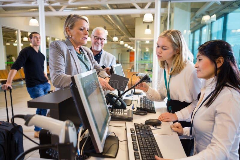 Коммерсантка держа пасспорт пока штат работая на авиапорте стоковое изображение rf