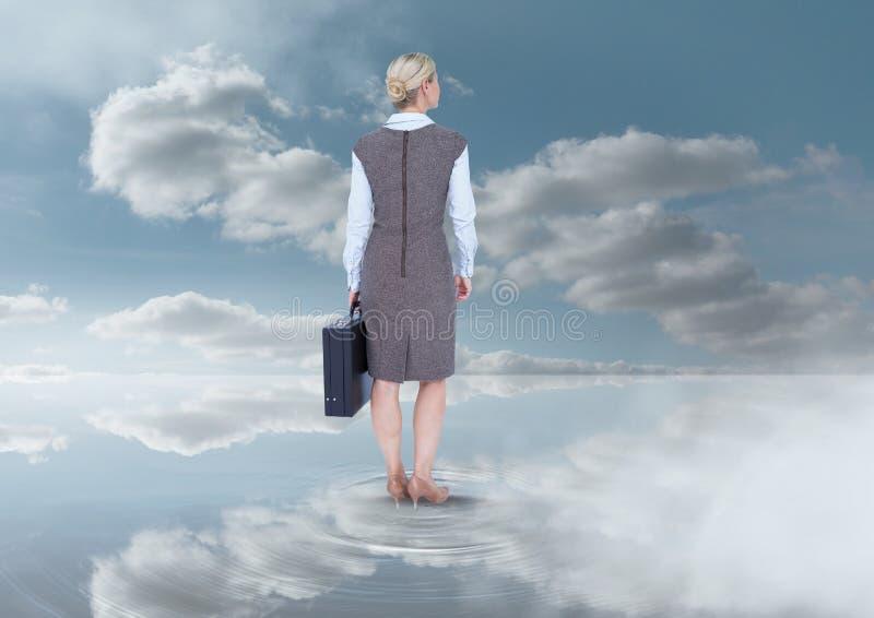 Коммерсантка держа портфель под облаками неба стоковые фото
