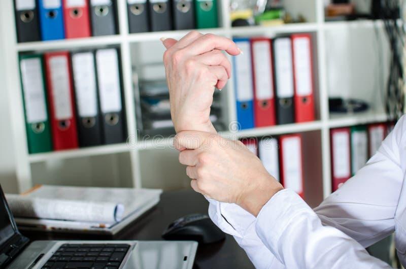 Коммерсантка держа ее тягостное запястье руки стоковые фотографии rf