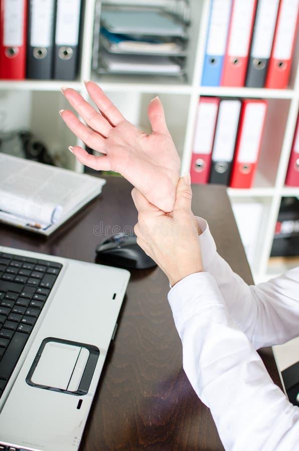 Коммерсантка держа ее тягостное запястье руки стоковое изображение rf