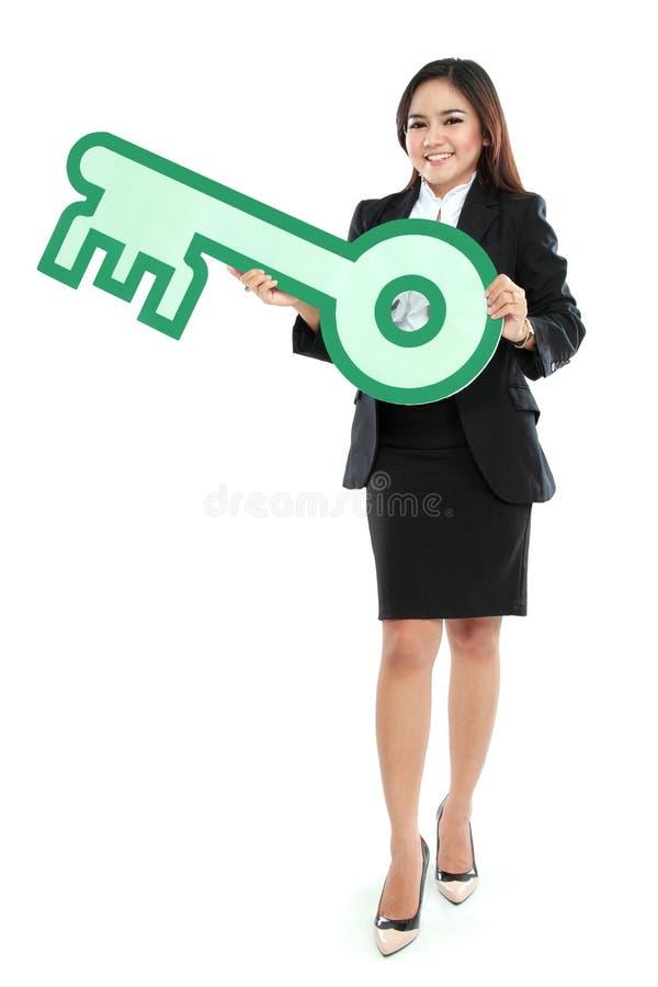 Коммерсантка держа знак ключа стоковые фото