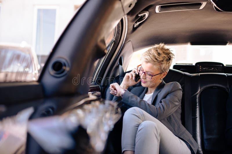Коммерсантка ждет в лимузине стоковая фотография rf