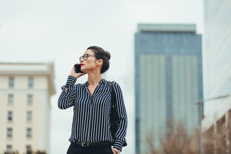 Коммерсантка идя outdoors с мобильным телефоном стоковые изображения