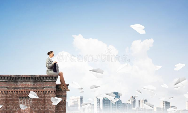 Коммерсантка или бухгалтер на верхней части и бумаге здания строгают летание вокруг Мультимедиа стоковое изображение