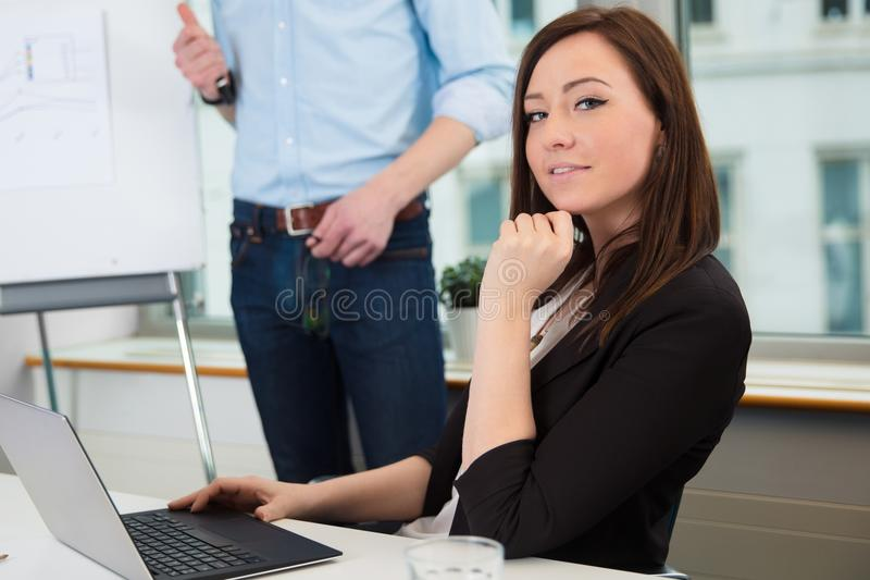 Коммерсантка используя компьтер-книжку пока коллега давая представление стоковое фото rf