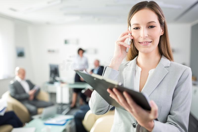 Коммерсантка используя мобильный телефон пока держащ доску сзажимом для бумаги в Offi стоковая фотография rf