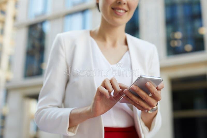 Коммерсантка используя Outdoors смартфона подрезала стоковое изображение