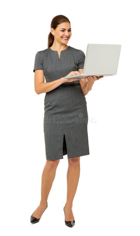 Коммерсантка используя компьтер-книжку над белой предпосылкой стоковые изображения rf