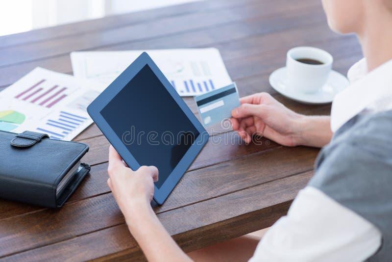 Коммерсантка используя ПК таблетки и держащ кредитную карточку стоковые фотографии rf