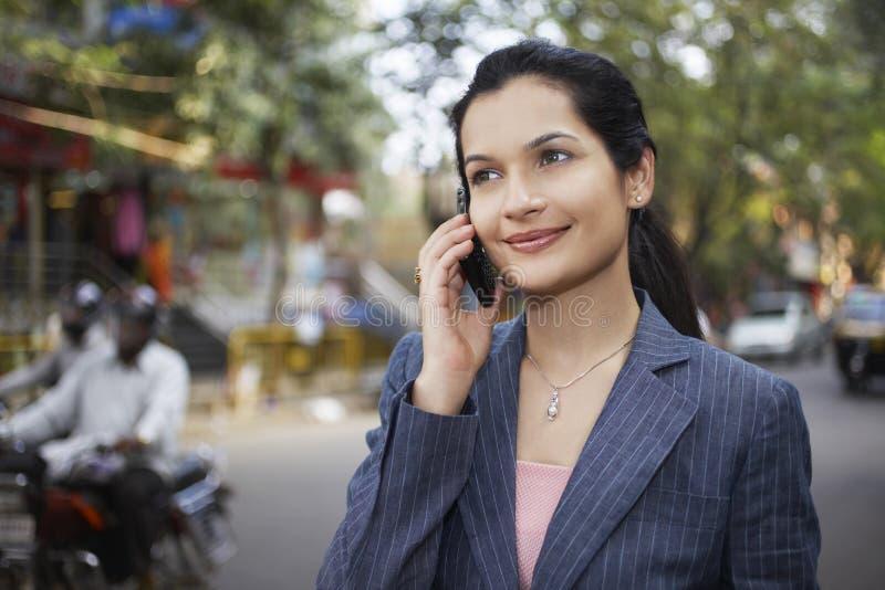 Коммерсантка используя сотовый телефон на улице города стоковые фотографии rf