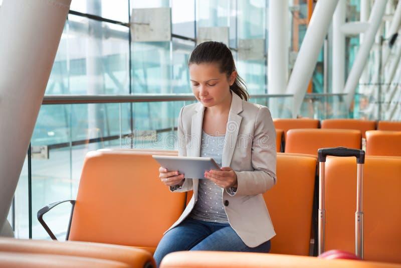Коммерсантка используя цифровую таблетку на лобби авиапорта стоковая фотография rf
