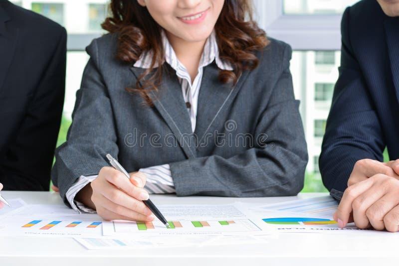 Коммерсантка и бизнесмены обсуждая документы на встрече стоковые фотографии rf