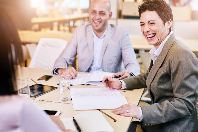 Коммерсантка и бизнесмен смеясь над счастливо к камере во время встречи стоковая фотография