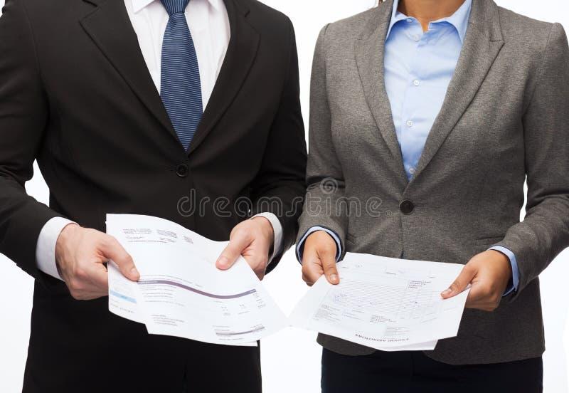 Коммерсантка и бизнесмен с файлами и формами стоковое фото