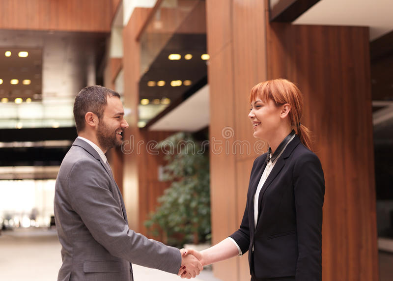 Коммерсантка и рукопожатие бизнесмена стоковое фото