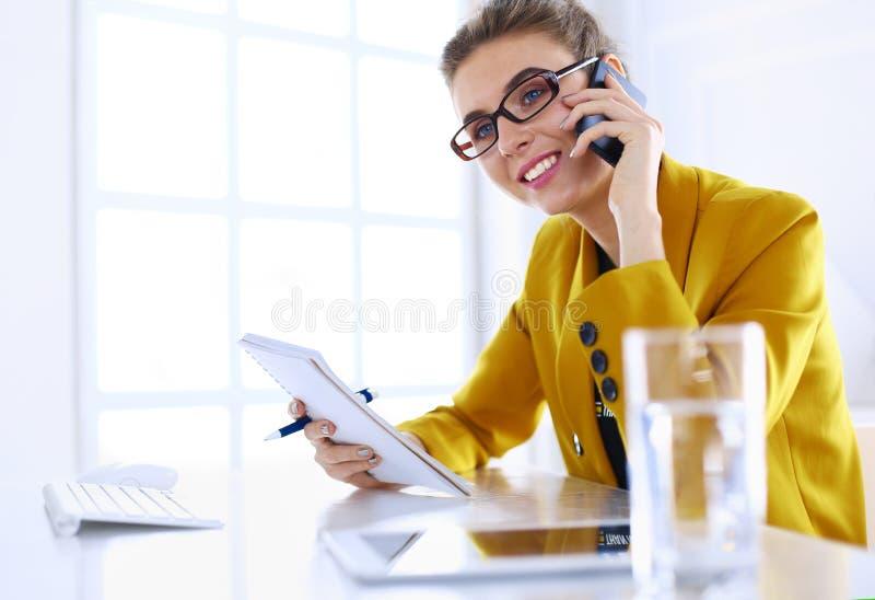 Коммерсантка концентрируя на работе, используя компьютер и мобильный телефон в офисе стоковое изображение
