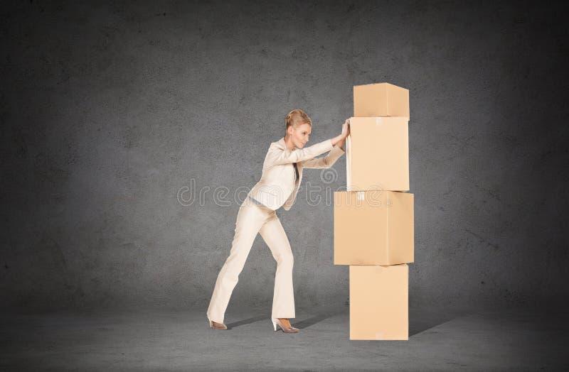 Коммерсантка нажимая башню картонных коробок стоковые изображения
