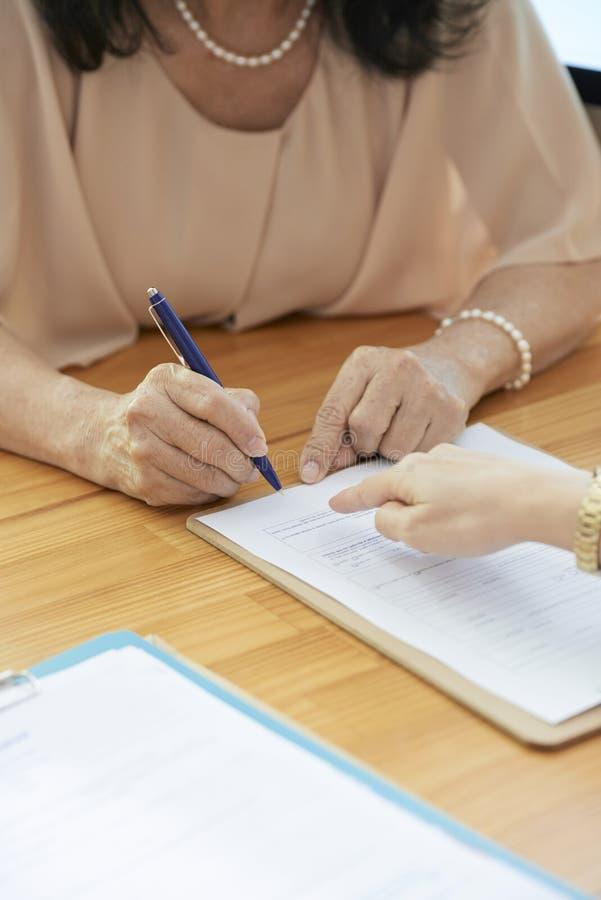 Коммерсантка подписывая контракт стоковые фото