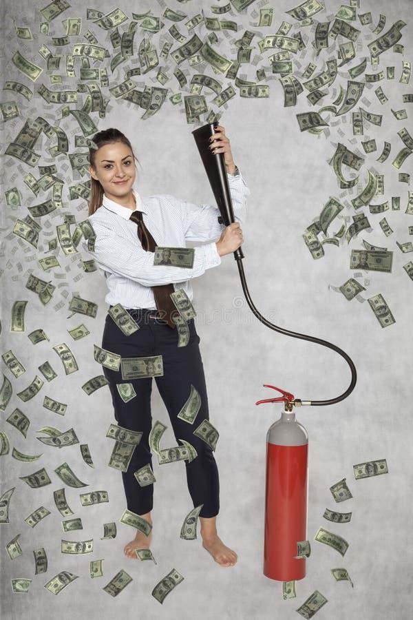 Коммерсантка под дождем денег от огнетушителя стоковое изображение