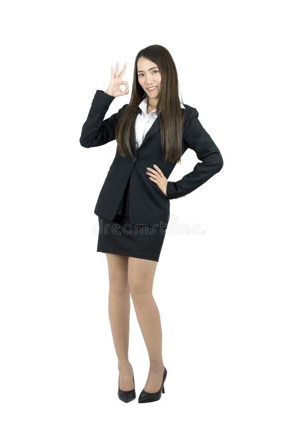 Коммерсантка показывая ОДОБРЕННЫЙ усмехаться знака руки счастливый Полное тело изолированное на белой предпосылке стоковое фото