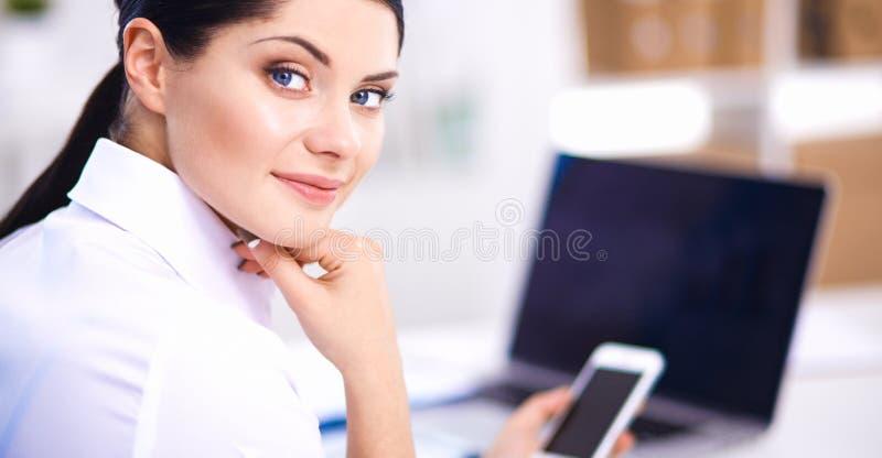 Коммерсантка посылая сообщение при smartphone сидя в офисе стоковые изображения