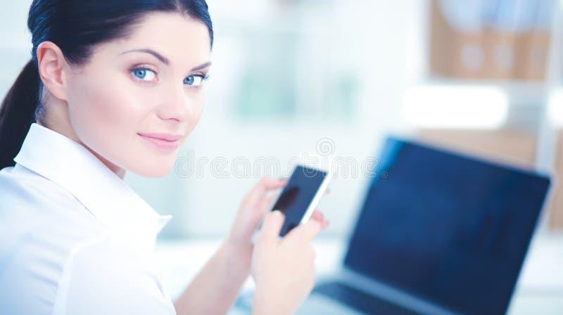 Коммерсантка посылая сообщение при smartphone сидя в офисе стоковое фото rf
