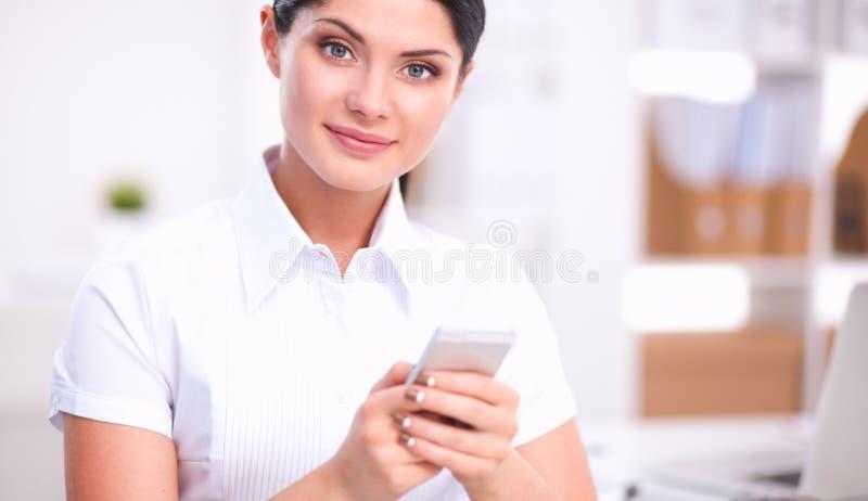 Коммерсантка посылая сообщение при smartphone сидя в офисе стоковая фотография
